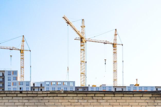 Costruzione di gru e edificio in costruzione dietro la recinzione