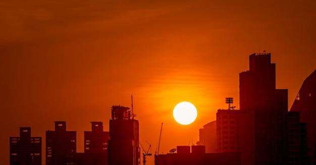 Edificio nel centro al crepuscolo con bel cielo al tramonto. silhouette di condominio e appartamento la sera. paesaggio urbano della costruzione e della gru di costruzione del grattacielo.