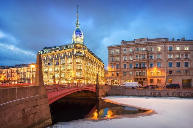 L'edificio del negozio esders e scheyfals a san pietroburgo alla luce dell'illuminazione invernale serale didascalia: negozio al ponte rosso, esders e schefals