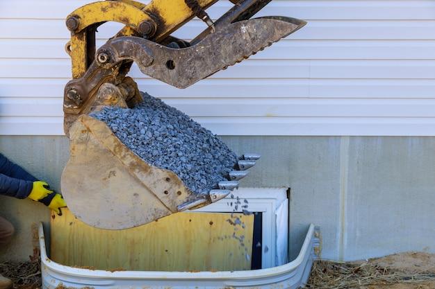 Finestra dei materiali da costruzione per la costruzione di scantinati spostando la paletta di ghiaia