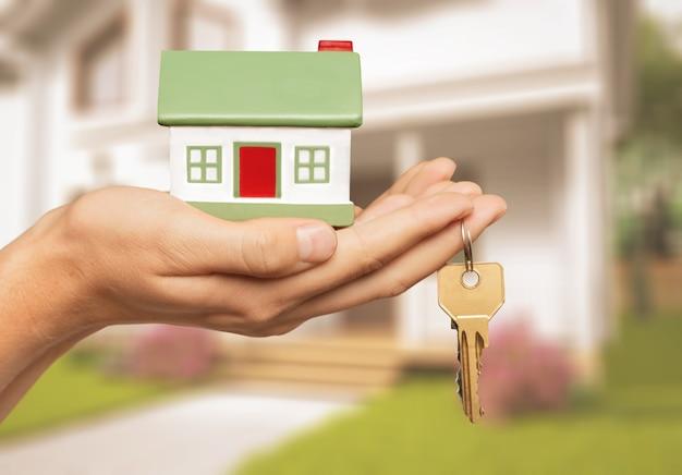 Costruzione, ipoteca, immobiliare e concetto di proprietà - primo piano del modello di casa che tiene la mano