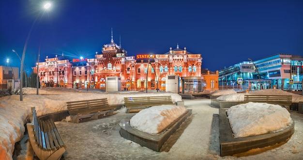 L'edificio della stazione ferroviaria di kazan e panchine nella neve in una notte di primavera. didascalia: stazione ferroviaria. fai un buon viaggio!