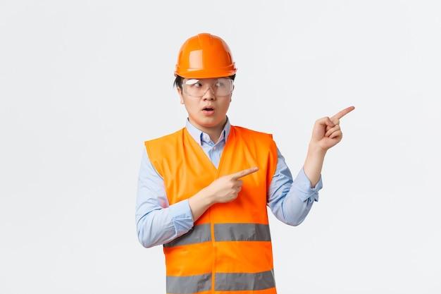 Settore edile e concetto di lavoratori industriali. responsabile edile maschio asiatico preoccupato e dubbioso, ingegnere in casco e abbigliamento riflettente che punta esitante nell'angolo in alto a destra.