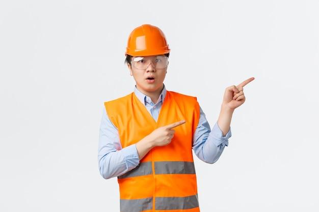 Settore edile e concetto di lavoratori industriali. impressionato e stupito direttore di costruzione asiatico, ingegnere in casco e abbigliamento riflettente che indica l'angolo in alto a destra, sfondo bianco.