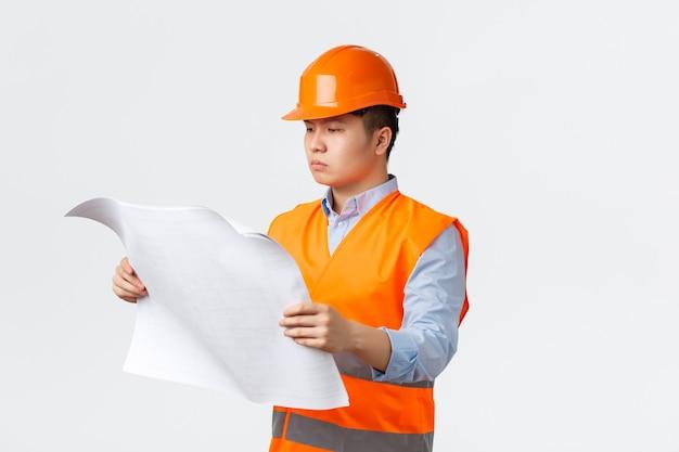 Settore edile e concetto di lavoratori industriali dall'aspetto serioso direttore di costruzione asiatico architetto s...