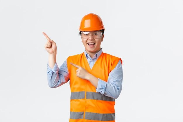 Settore edile e concetto di lavoratori industriali. sorridente allegro architetto asiatico, ingegnere capo in casco di sicurezza e giacca riflettente, puntando le dita nell'angolo in alto a sinistra, mostrando banner