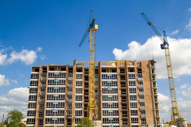 Cantiere con due gru a torre industriali che lavorano alla costruzione del nuovo edificio alto in mattoni su cielo blu luminoso e alberi verdi