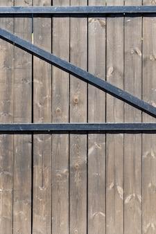Costruito con cancelli a assi in un fienile, collegati da un fissaggio in metallo nero, primo piano dall'interno