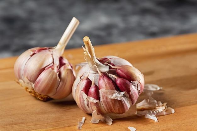 Bulbo o spicchio d'aglio su base in legno. tipo di aglio viola, solitamente usato come condimento negli alimenti.