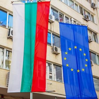 La bandiera nazionale bulgara e la bandiera dell'unione europea sono appese a un edificio per uffici nella città di sofia, in bulgaria