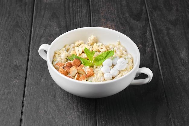 Porridge di bulgur con mandorle e nocciole e mirtilli rossi in panatura di zucchero a velo