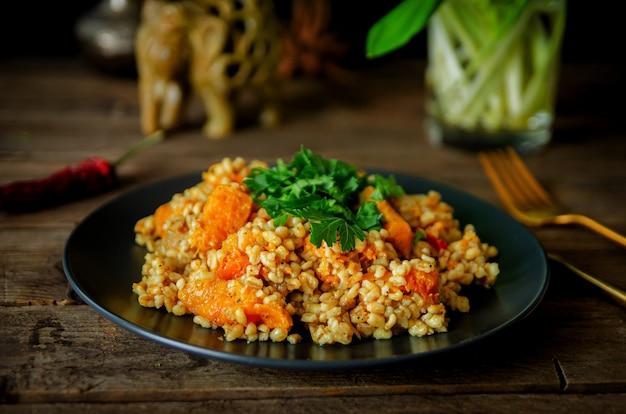 Bulgur con zucca su un tavolo di legno. ricette vegetariane della cucina indiana.