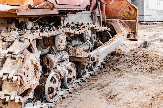 Primo piano della macchina cingolata del bulldozer cingoli potenti del bulldozer. macchine edili per il livellamento del terreno. macchinari pesanti da costruzione.