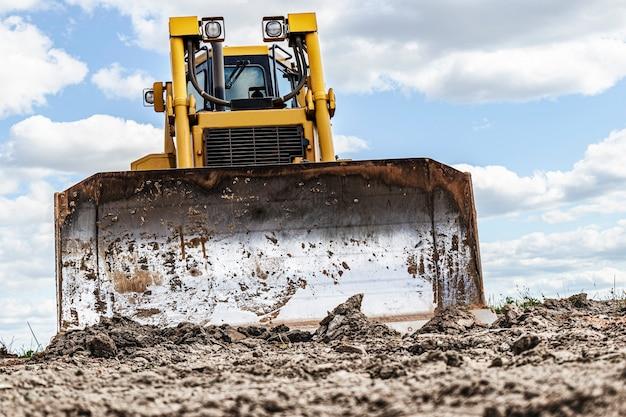 La macchina del bulldozer sta livellando il cantiere. il movimento terra con il bruco sta muovendo la terra. avvicinamento. macchinari pesanti da costruzione.