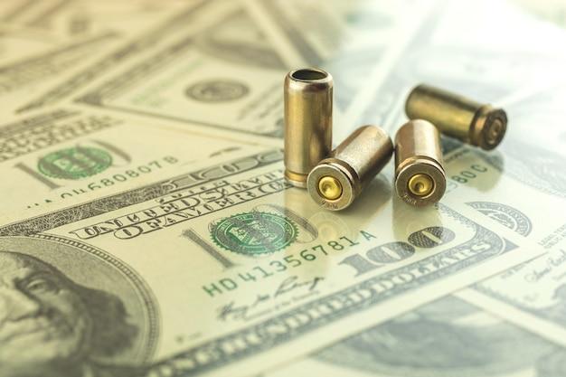 Proiettile sullo sfondo del dollaro, denaro criminale e corruzione, concetto di commercio illegale foto