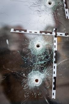 Fori di proiettile in una vetrina segnata con un nastro della polizia