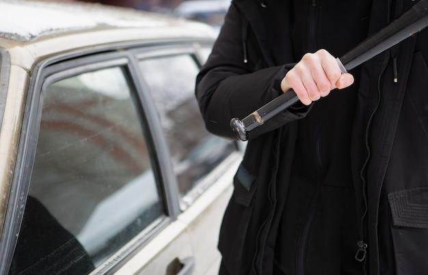 Un bullo tenta di rompere il finestrino di una macchina con una mazza da baseball