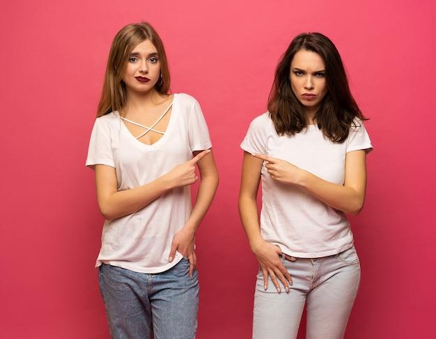 Bullismo, amicizia e concetto di persone - due giovani donne arrabbiate in piedi su sfondo rosa, due adolescenti che hanno una lotta