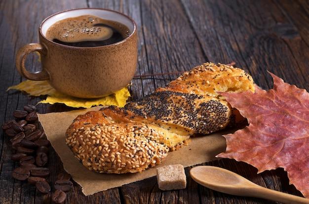 Panino con semi di lino e papavero e tazza di caffè caldo sul tavolo