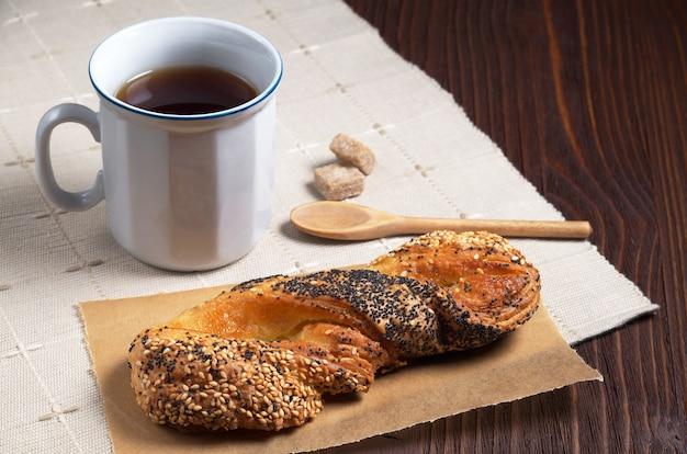 Panino con semi di lino e papavero e tazza di tè sul tavolo