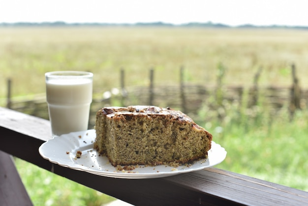 Panino con semi di papavero con un bicchiere di latte. latte in un bicchiere e torta di semi di papavero su un campo