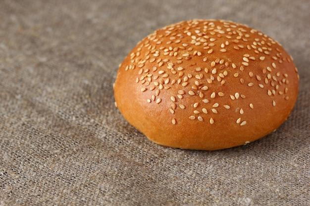 Panino con semi di sesamo, uno rotondo sulla tovaglia ruvida di tela.