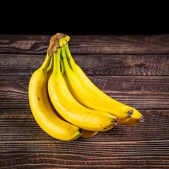Mazzo di banane isolato su uno sfondo di legno