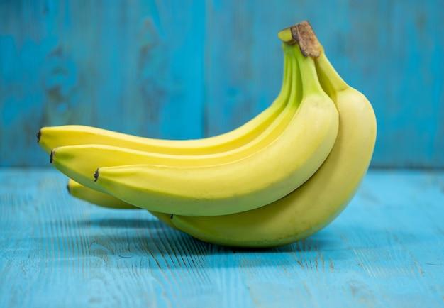 Mazzo di banane su fondo blu di legno
