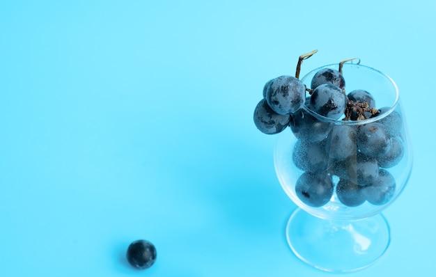 Grappolo d'uva nera nel bicchiere blu su sfondo sfocato