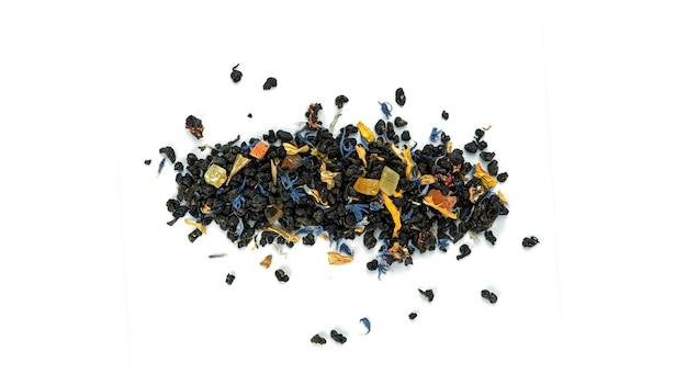 Mazzo di foglie di tè nero con frutti su sfondo bianco
