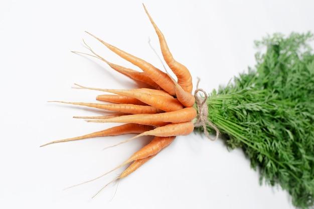 Mazzo di carote legato con una corda isolata su sfondo bianco. vista ravvicinata.