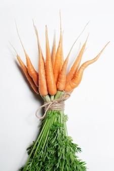 Mazzo di carote legato con una corda su sfondo bianco.
