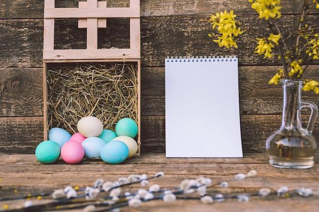 Un mazzo di uova colorate con fieno e un taccuino sopra. sullo sfondo di una vecchia tavola. concetto sul tema del giorno di pasqua.