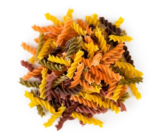 Un mucchio di pasta colorata a spirale su un bianco