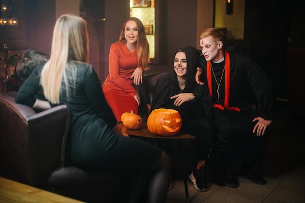 Un gruppo di quattro amici che si divertono a festeggiare halloween al bar. guy è vestito da terribile prete e mostro. bella ragazza sexy in abito rosso. zucca intagliata sul tavolo