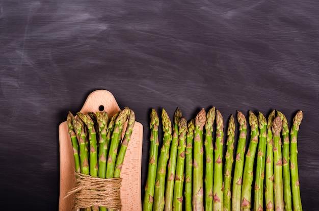 Un mucchio di asparagi freschi su un tagliere e gambi su una lavagna nera con posto per il testo. raccolto stagionale primaverile. lay piatto, copia spazio. concetto di cibo sano. vista dall'alto. avvicinamento