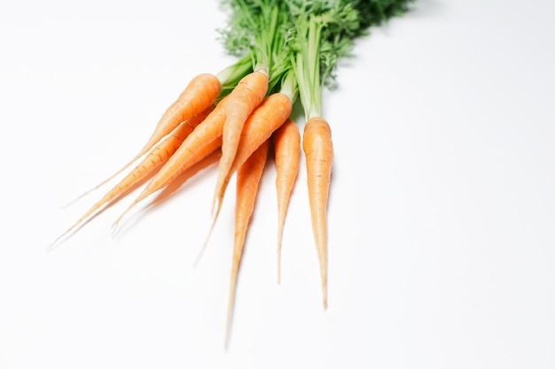Mazzo di carote fresche sul tavolo bianco.