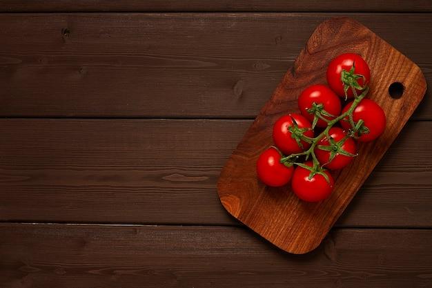 Un mazzo di pomodorini freschi su un tavolo in legno marrone non visualizza persone