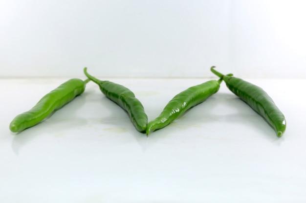 Mazzetto di peperoncino verde fresco su sfondo bianco