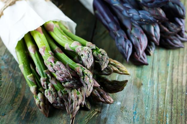 Mazzo di asparagi freschi viola e verdi sulla tavola di legno