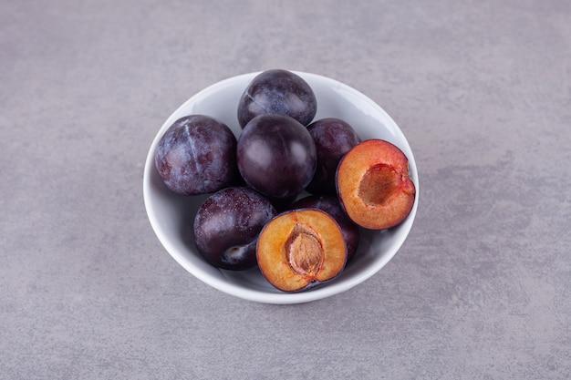 Mazzo di prugne viola fresche poste sulla superficie della pietra. Foto Premium