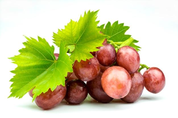 Grappolo di uva rosa fresca e matura con foglie verdi isolato su priorità bassa bianca.