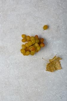 Un grappolo d'uva e una foglia secca di un cespuglio d'uva su un tavolo di pietra. vista dall'alto.