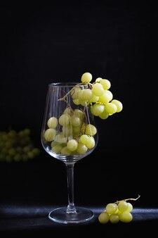 Grappolo d'uva verde servito in un bicchiere di vino sul tavolo nero scuro in un raggio di luce contro il muro nero