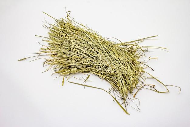 Mazzo di fieno isolato su fondo bianco. erbe secche, cibo per animali domestici