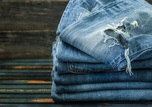 Mazzo di jeans sul tavolo di legno, vestiti alla moda