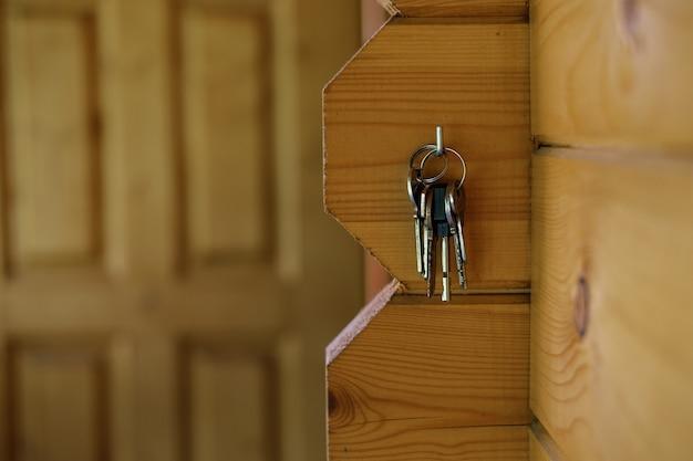 Un mazzo di chiavi della nuova casa è appeso a un gancio sullo sfondo della porta d'ingresso.