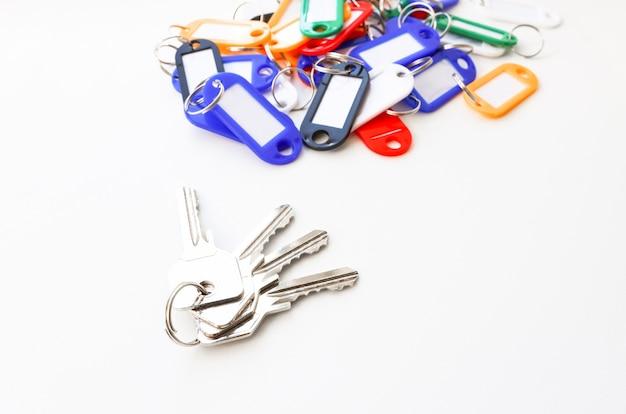 Un mazzo di chiavi con portachiavi di diversi colori e un posto per un'iscrizione su sfondo bianco white