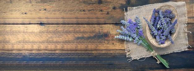 Mazzo di fiori di lavanda accanto a un piccolo cesto pieno di petali su un tessuto naturale su fondo in legno