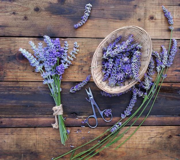 Mazzo di fiori di lavanda accanto a un piccolo cesto pieno di petali con forbici su fondo in legno